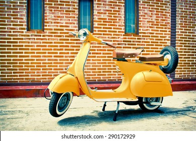 Bangkok,THAILAND - 2015 April 19 : Yellow classic motorcycle on red brick background