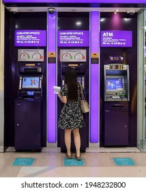 Bangkok,Thailand - 31March2021 - Asian woman at SCB Bank automated banking station - one stop smart Thai bank customer self-service financial machine (ATM , CDM, book update)-convenient 24 hrs service