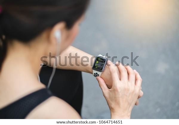 Bangkok,Thailand ,9 Apr 2018 : Woman choose Activity App outdoor run program on Apple Watch before run Working out