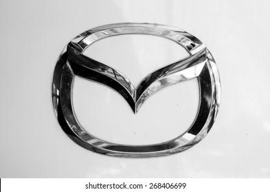 "BANGKOK,THAILAND - April 11,2015 : Logo of the brand ""Mazda"" on white car"