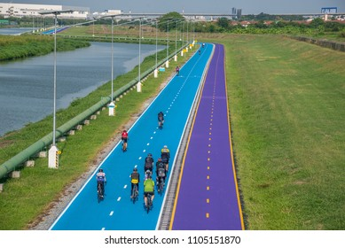 Bangkok,Thailand - April 14,2018 :  Unidentified people bicyclists biking in motion at new blue and purple bicycle lane of Suvarnabhumi international airport,Bangkok,Thailand.