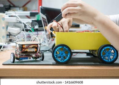 Bangkok/Thailand - April 17, 2018: Close up of teenage boy's hand working on robotic projects. Wirelessly controlled car with Micro:bit board. STEM education
