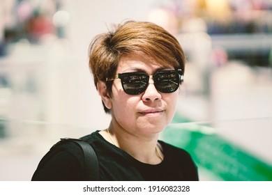 Bangkok-Thailand, April 6 2018: Asian woman short haired  wearing black glasses ,T-shirt with bokeh background