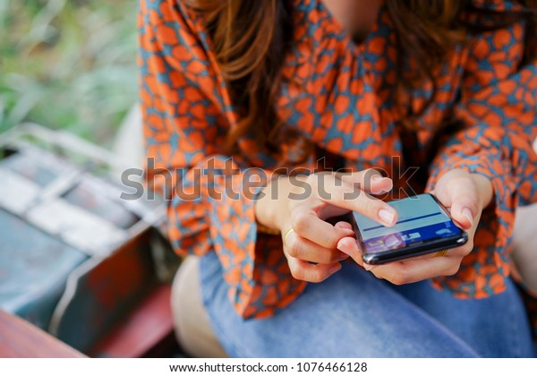 Bangkok,Thailand- April 7,2018 : close up woman hand holding smartphone (Iphone X) and show facebook application on screen , media network technology and social distance concept