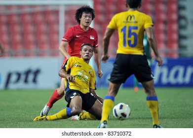 BANGKOK,THAILAND - AUG 24  ; Pratum Chutthong (Y) of Thailand during friendly football match between Thailand (Y) and Singpore (R) at Rajamagala Stadium on Aug. 24, 2011  Bangkok Thailand
