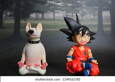 Bangkok,Thailand - August 1,2018: The setting of famous Japanese animation Dragon Ball, an action figure  of young Son Goku doing Yoga with dog.