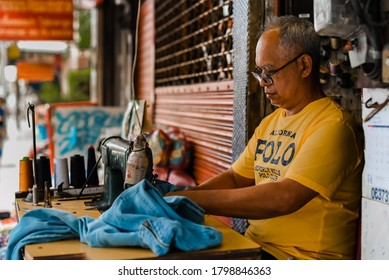 BANGKOK/THAILAND - AUGUST 2020: a middle aged asian street tailor wearing glasses, repairing clothes using sewing machine in Phrakanong. Working class had to work hard leading a simple life.