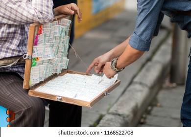 Bangkok,Thailand - August 31, 2018 : Unidentified man buying Thai lottery at market.