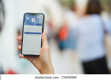 Bangkok,Thailand- December 17,2017 : close up woman hand holding smartphone (Iphone X) and show facebook application on screen , social median and technology concept