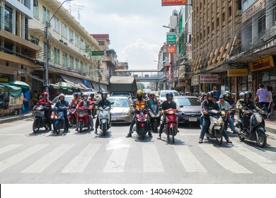 Bangkok/Thailand - December 6, 2018: Front view of motorcycles and cars behind zebra crossing line in heavy traffic during red light waiting for green light.