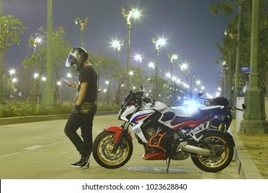 Bangkok,Thailand - February 10,2018 : Man standing near motorcycle on the road in bangkok,Thailand.