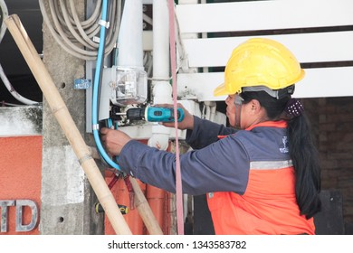 BANGKOK,THAILAND, FEBURAY 27,2019 ; Electricians are using drills to install electric meter, measuring unit on pole.