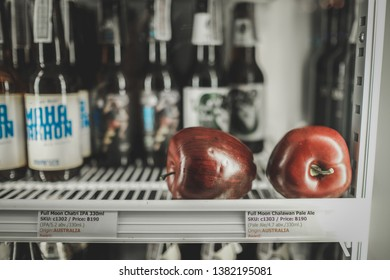 Bangkok/Thailand - Jan 12 2019 : two red apples with a lot of craft beer bottles inside white refrigerator, microbrewery IPA craft beer