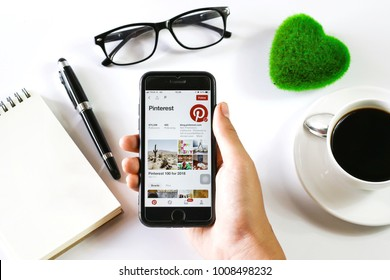 BANGKOK,THAILAND -January 14,2018: Hand holding Apple iPhone7 with Pinterest application on the screen with Notebook, Coffee cup, Pen, Glasses and Green Heart on White background