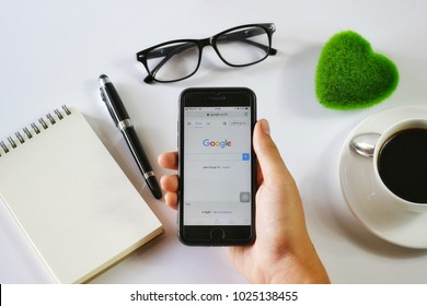 BANGKOK,THAILAND -January 14,2018: Hand holding Apple iPhone7 with Google application on the screen with Notebook, Coffee cup, Pen, Glasses and Green Heart on White background