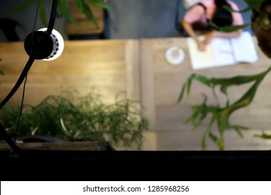 Bangkok/thailand - January 14,2019 : A blurred shot of a young energetic asian woman working in 24 hours cafe or co-working space  shared wood table with black space and a lamp as foreground