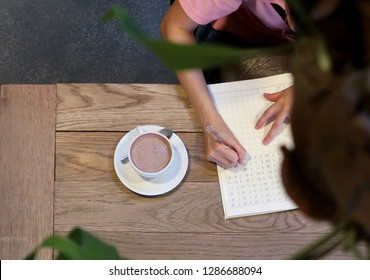 Bangkok/thailand - January 14,2019 : A young asian woman working with her paper work in 24 hours cafe or co-working space with some green plant as foreground.