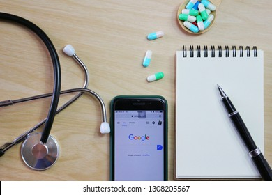 BANGKOK,THAILAND -January 21,2019 : Flat lay photo with Google application on the screen Stethoscope , notebook , wooden spoon and Medicine capsule on wooden background