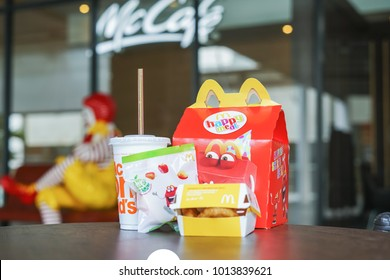 BANGKOK,THAILAND - JANUARY 9,2018 : Happy meal set on desk ,in soft focus, with blurred Ronald McDonald at McDonald's restaurant