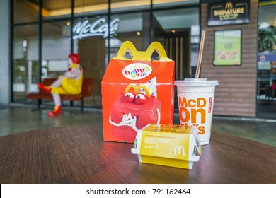 BANGKOK,THAILAND - JANUARY 9,2018 : Happy meal set ondesk ,in soft focus, with blurred Ronald Mcdonald at McDonald's restaurant on