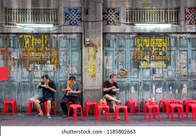 Bangkok-Thailand JUL 6 2017: Unidentified Thai Asian people who' re sit on red chair for eating curry rice street food on footpath at Chinatown (Yaowarat) on Bangkok, Thailand