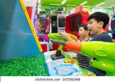 Bangkok/Thailand - July 14, 2019: Cute and adorable little Asian boy and smart looking preteen brother playing water shooting arcade game with joy and fun in shopping mall.9