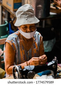 BANGKOK/THAILAND - JULY 2020: old female street tailor wears mask and a Panama hat, sits next to sewing machine at Wongwian Yai Railway station during COVID-19 coronavirus outbreak.