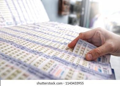 Bangkok,Thailand - July 27, 2018: Customer choosing Thai national lottery ticket.Thai government lotto distributes many cash prizes two period per month.