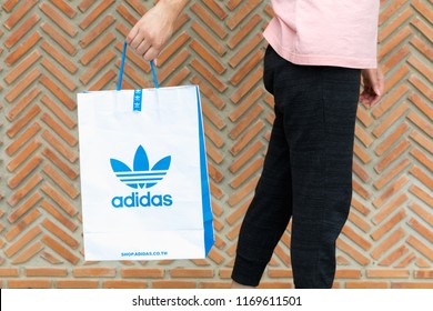 BANGKOK,THAILAND - JULY 7,2018:A woman holding paper bag Adidas original logo for product Adidas original. Adidas - German industrial group specializing in the production of athletic footwear, apparel