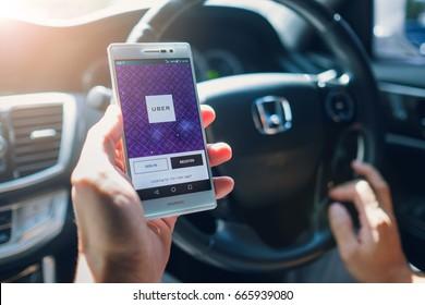 BANGKOK,THAILAND - JUN 24,2016 : Asian man holding Uber driver app showing on Huewei P7 smartphone inside the car, Hand of male driving Honda car, Uber is smartphone app-based transportation network.