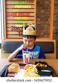 BANGKOK,THAILAND JUNE 15,2019: Photo of asian boy in paper crown is drinking and have full set meal of hamburger ,french fried and chicken in Burger King restaurant in daytime