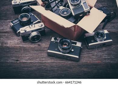 BANGKOK,THAILAND - JUNE 19,2017 : Retro film cameras on wooden background.