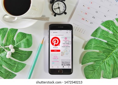 BANGKOK,THAILAND - June 2,2019: Flat lay photo with Apple iPhone opened Pinterest app on the screen with Coffee cup ,Calendar ,Earphone ,Tropical Leave and Clock on White background
