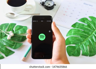 BANGKOK,THAILAND - June 2,2019: Hand Holding Apple iPhone opened Spotify app on the screen with Coffee cup ,Calendar ,Earphone ,Tropical Leave and Clock on White background