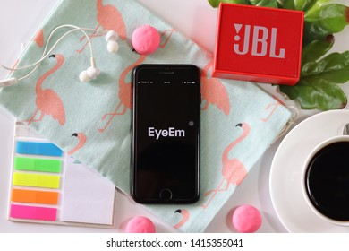 BANGKOK,THAILAND - June 2,2019:Flat lay photo with Apple iPhone opened Eyeem app on the screen with Coffee cup ,Loudspeaker ,Earphone ,Tropical Leave  and macaroon on White background