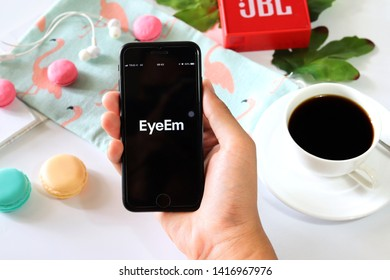 BANGKOK,THAILAND - June 2,2019:Hand holding Apple iPhone  opened EyeEm app on the screen with Coffee cup ,Loudspeaker ,Earphone ,Tropical Leave and macaroon on White background