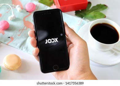 BANGKOK,THAILAND - June 2,2019:Hand holding Apple iPhone  opened Joox app on the screen with Coffee cup ,Loudspeaker ,Earphone ,Tropical Leave and macaroon on White background