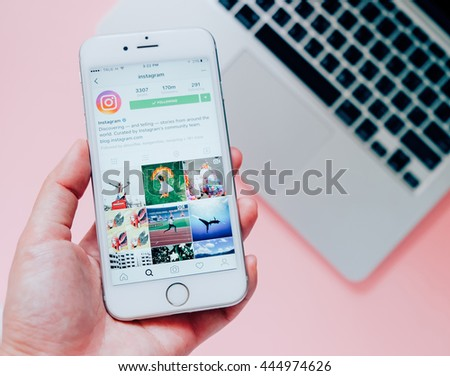 BANGKOK,THAILAND - June 28,2016: Hand holding Apple iPhone6s with Instagram application on the screen with laptop background. Instagram is a photo-sharing app for smartphones.