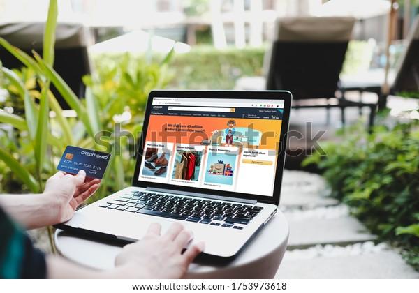 BANGKOK,THAILAND - JUNE 6, 2020 :A woman using laptop showing Amazon logo and credit card shopping online. Amazon.com, Inc. American international electronic commerce company.