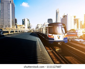 Bangkok,Thailand - June10,2018 :: BTS or Bangkok Skytrain moves to the station before sunset with a panorama cityscape scene of Bangkok, Thailand