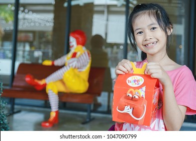 BANGKOK,THAILAND - MARCH 10,2018 :little Asian girl holding happy meal box at McDonald's restaurant