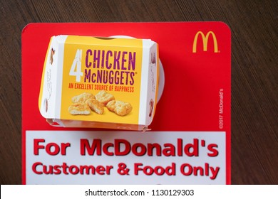 BANGKOK,THAILAND - MARCH 10,2018 : top view of Mc NUGGETS on brown desk  with phrase For McDonald's Customer & Food Only