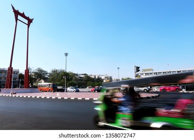 Bangkok/Thailand - March 11,2019 :A blurred moving TUK TUK - a famous traditional unique vehicle / symbol of Thailand tourism moving pass the Giant Swing (Thai: Sao Ching Cha) red religious structure.