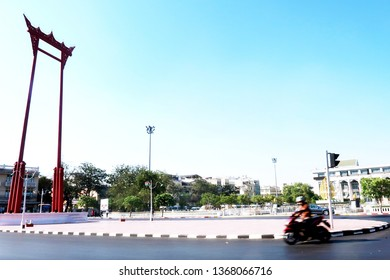 Bangkok/Thailand - March 11,2019 : A blurred moving motorcycle riding pass the Giant Swing (Thai: Sao Ching Cha) Thailand red religious iconic structure.