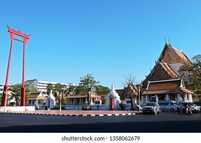 Bangkok/Thailand - March 11,2019 : The Giant Swing (Sao Ching Cha) towering red religious structure and  beautiful buddhist temple WAT SUTHAT on the right.