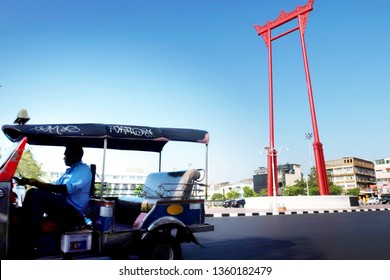 Bangkok/Thailand - March 11,2019 :TUK TUK - famous unique iconic vehicle/Thai tourism symbol, on downtown street  in front of the Giant Swing (Sao Ching Cha) iconic red religious towering pillars.