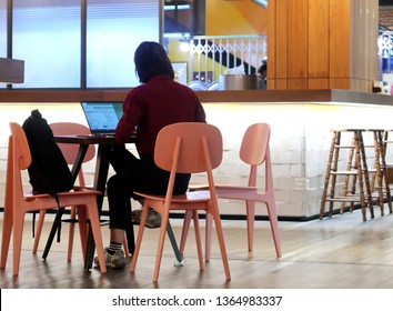 Bangkok/Thailand - March 21,2019: An Asian girl working with her laptop at the shopping mall co-working space area.
