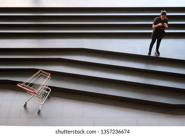 Bangkok/Thailand - March 21,2019: An Asian woman with her smartphone and an empty red shopping cart at the shopping mall, concept of online lifestyle vs offline retail shopping