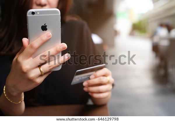 Bangkok,Thailand  - May 14,2017 :close up asian woman hand using iphone mobile device for pay online with credit card concept.