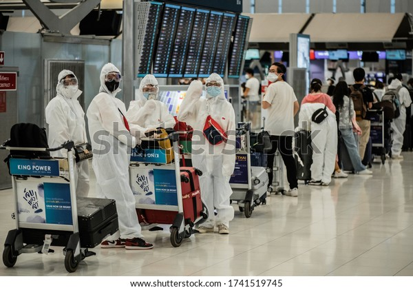 BANGKOK/THAILAND - MAY 26,2020: Asian passengers in protective overall and masks at Suvarnabhumi Airport going to check-in for repatriation flights and waving good bye during COVID-19 outbreak
